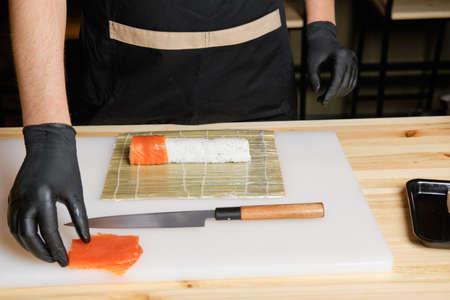 Male hand put salmon while preparing rolls