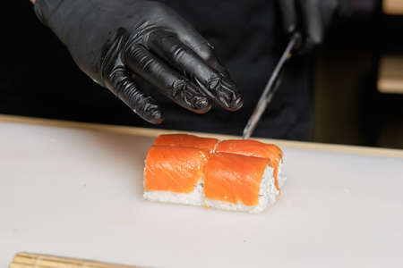 Male hand cutting with knife  salmon rolls