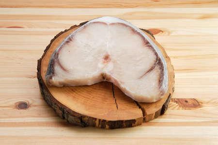 Frozen blue shark steak on wooden table