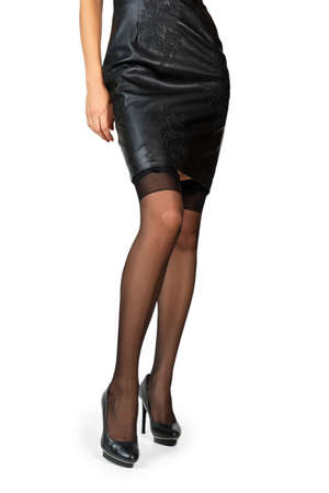 Beautiful female legs in black stockings and leather dress isolated on white