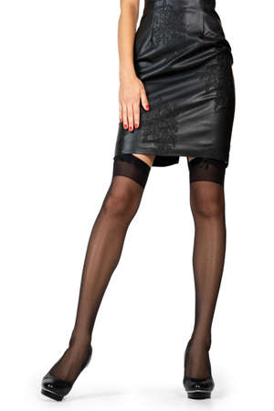 Beautiful female legs in black stockings and eco leather dress isolated on white