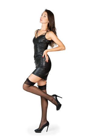 Pretty girl in eco leather dress and stockings posing with one leg lifted up in profile