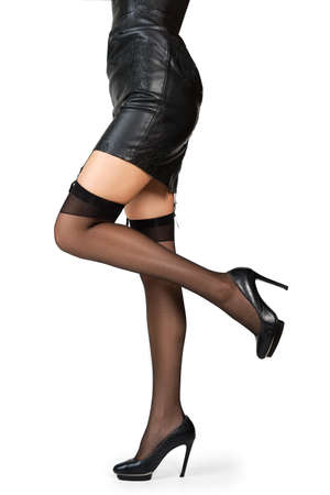 Legs of woman in stockings and garter posing with one leg lifted up in profile