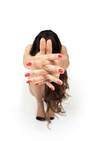 Squatting girl with hands pulled forward and crossed fingers (photo with shallow depth of field) Imagens