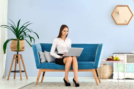 Young woman in black skirt and white blouse using laptop while sitting on comfortable sofa