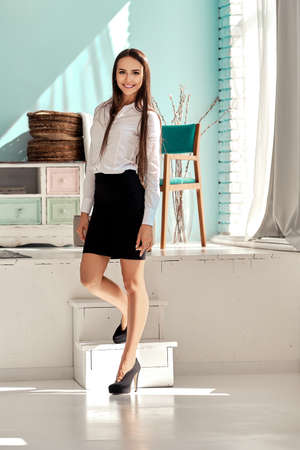 Pretty girl in black skirt and white shirt descending the stairs