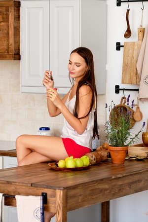 Happy girl sitting on kitchen table and eating yogurt Imagens