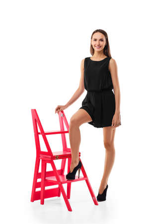 Pretty girl standing near folding stepladder chair with one leg on step isolated on white Imagens