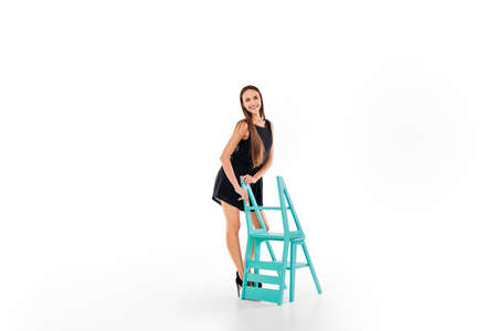 Pretty girl standing near folding stepladder chair  isolated on white