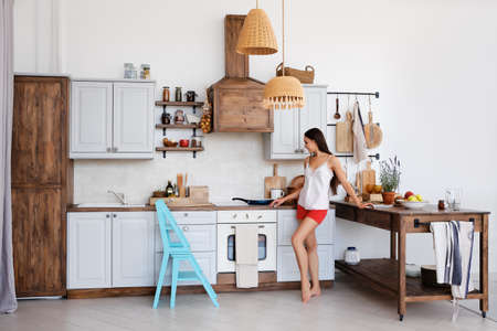 Lifestyle photo of cute girl standing by the stove in the kitchen, cooking and smelling nice aromas from frying food Imagens