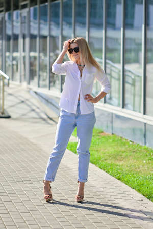 Street style fashion - lady in white shirt and boyfriend jeans walking along business centre Imagens