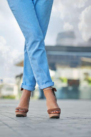Crossed female legs in blue jeans and suede shoes on pavement