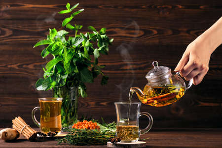 Pouring hot herbal tea with sea buckthorn