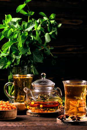 Low key photo of  hot herbal tea with sea buckthorn and mint