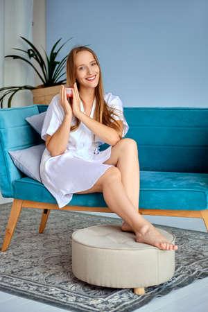 Schönes Mädchen, das Fußcreme in den Händen hält und auf der Couch in weißem Seidengewand sitzt