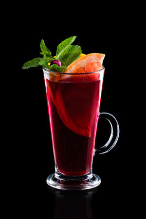 Glass of hot rose tea with grapefruit and mint isoalted on black. (Photo with clipping path)