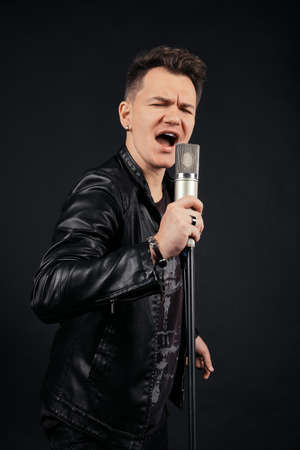 Low key portrait of man singing and holding microphone Imagens