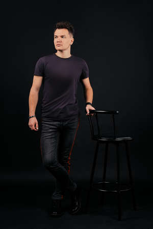 Full length portrait in low key of man standing near the chair
