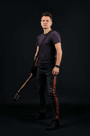 Full length portrait in low key of musician standing with guitar