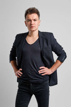 Portrait of serious man in jeans, t-shirt and fitted jacket with hands on waist