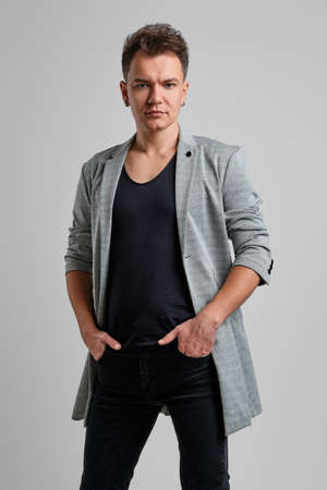 Portrait of a handsome man wearing wool jacket, black shirt and jeans