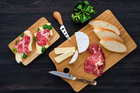 Overhead view of camembert sandwich with smoked bacon on dark wooden table. Foto de archivo - 137995791