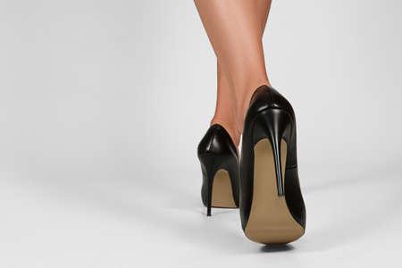 Vista baja de piernas femeninas en zapatos de tacón. Vista posterior de la dama que camina.