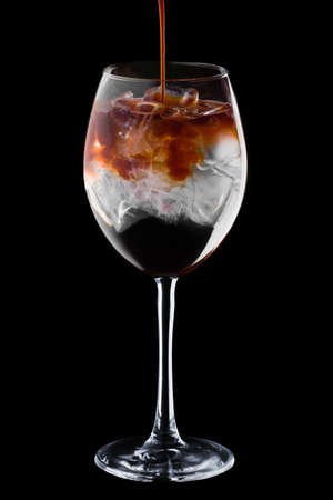 Pouring spresso in cocktail with tonic in wine glass isolated on black background