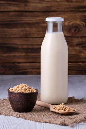Closed bottle of soy milk with small bowl and spoon with soya beans 스톡 콘텐츠