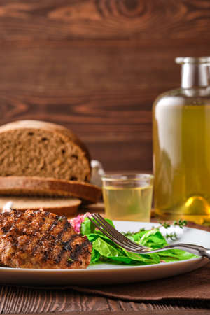 Grilled beef cutlet with fresh salad, brown bread and moonshine on rustic wooden table