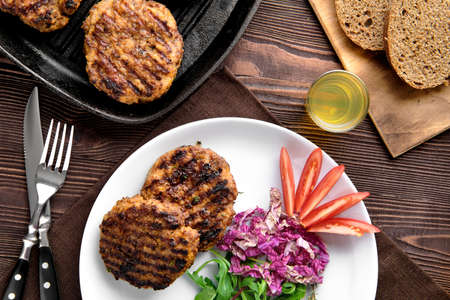 Top view of country dinner with cutlet and fresh salad, brown bread and moonshine on rustic wooden table Stock Photo