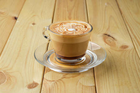 Cappuccino in transparent glass cup on wooden table