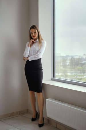 Full length view of young woman standing near window in white shirt and black tight skirt