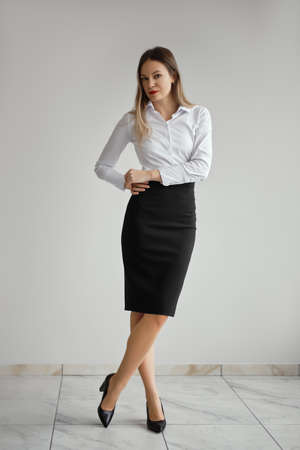 Slim girl in white shirt and black tight skirt posing near the wall Standard-Bild