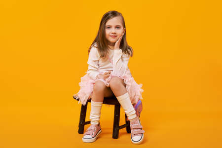 Young girl in tulle skirt and white pullover sitting on small wooden stool on bright yellow background