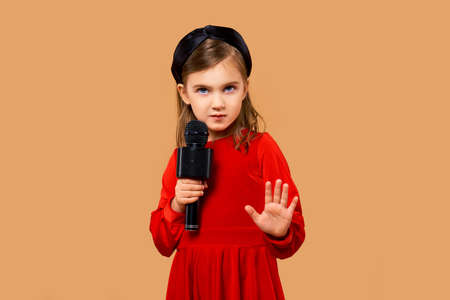 Artistic girl in red dress singing in karaoke microphone