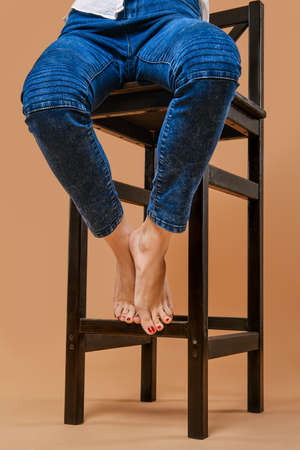 Cropped photo of bare feet of a girl sitting on a chair