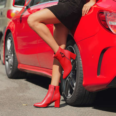 Female legs in red shoes leaning against the car Stock Photo