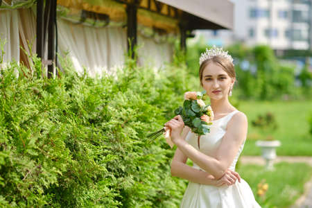 Portrait of pretty bride with coronet in hair outdoor near ceremony pavilion