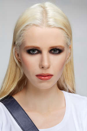 Girl with long straight white hair and defiant makeup, blue eyes and red lips. Face with freckles.