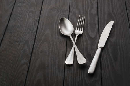 Vintage knife, fork and spoon on dark wooden table Archivio Fotografico