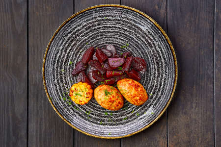 Top view of plate with fried pork cutlet with roasted beetroot slices and grilled maize on dark wooden table  Zdjęcie Seryjne