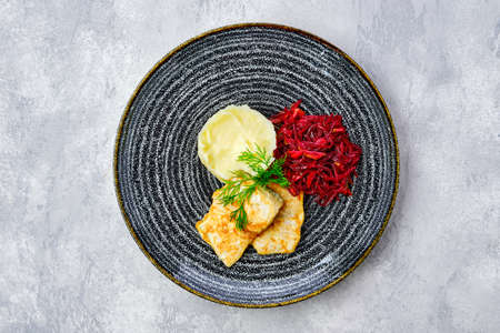 Top view of fried hake in breading with mashed potato and roasted beetroot