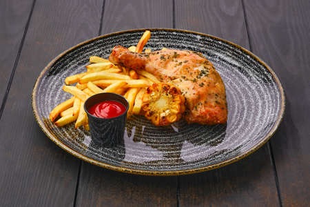 Baked chicken thigh with french fries, grilled corn and ketchup on dark wooden table