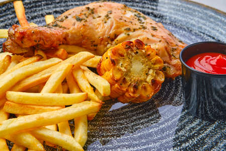 Close up view of baked chicken thigh with french fries, grilled corn and ketchup on dark wooden table
