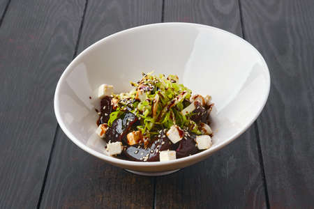 Salad with boiled beetroot, fresh cabbage, feta cheese, sesame and barbecue sauce on dark wooden table