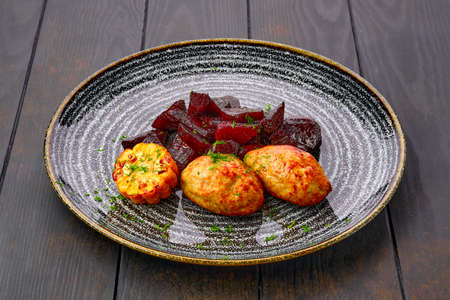 Plate with fried pork cutlet with roasted beetroot slices and grilled maize on dark wooden table