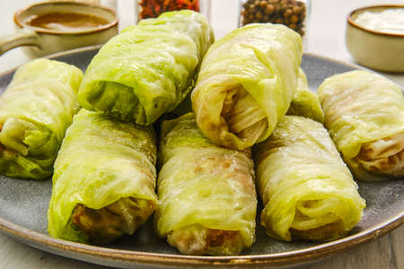 Close up view of rolled cabbage leaves stuffed with ground meat, rice and onion on black background