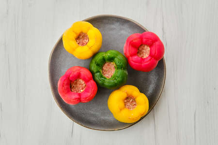 Top view of colorful bell pepper stuffed with meat and rice on white wooden table