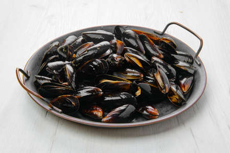 Big plate with frozen cooked whole shell mussels Standard-Bild